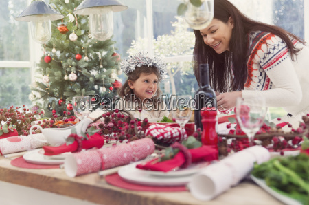 mother and daughter setting christmas table
