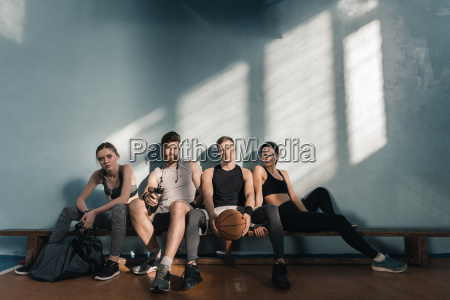 serious sporty men and women sitting
